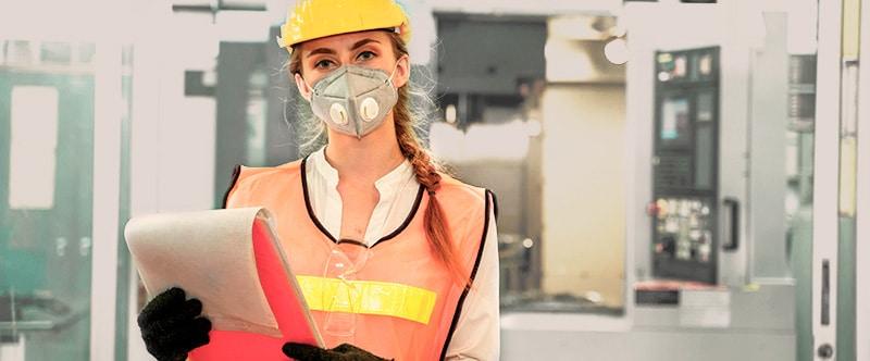 Mujer con material de seguridad en una fábrica